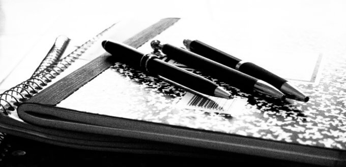 A photo of 3 pens on a composition book