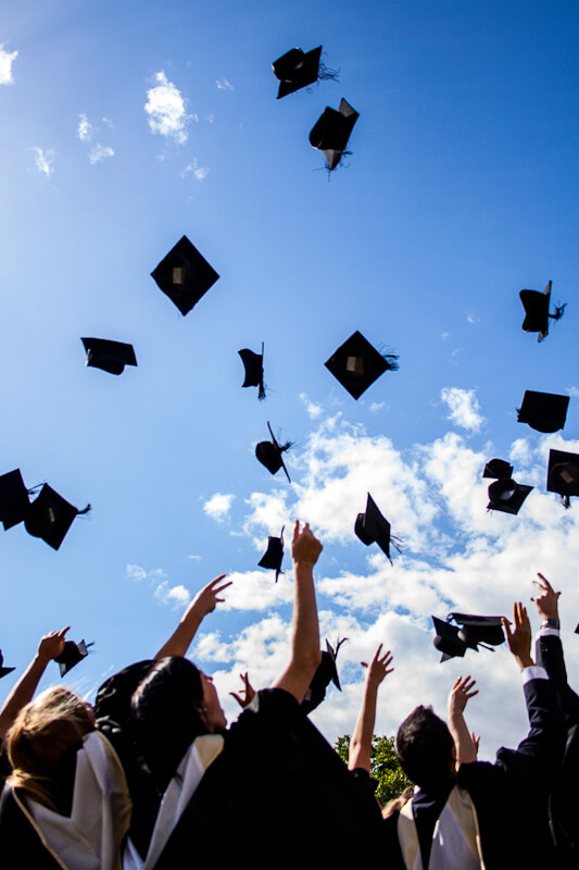 Graduation: Students in gowns throwing black caps in the air, against a blue sky